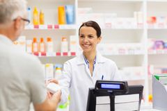 Apothecary selling drug to senior man at pharmacy. Medicine, pharmaceutics, health care and people concept - apothecary and senior men customer buying drug at royalty free stock photos