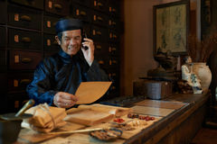 Apothecary. Senior Asian man taking on phone from apothecary Royalty Free Stock Images