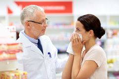 Apothecary and sick customer at pharmacy. Medicine, healthcare and people concept - senior apothecary with drug and female customer having cold and blowing nose Royalty Free Stock Images
