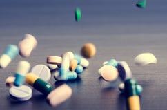 Apotheekachtergrond op een donkere lijst Levitatiepillen Tabletten op een donkere achtergrond die die neer vallen Pillen Geneesku Stock Afbeeldingen