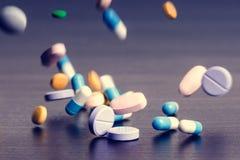 Apotheekachtergrond op een donkere lijst Levitatiepillen Tabletten op een donkere achtergrond die die neer vallen Pillen Geneesku Royalty-vrije Stock Afbeeldingen