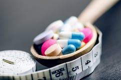 Apotheekachtergrond op een zwarte lijst met het meten van band Tabletten op een houten lepel Pillen Geneeskunde en gezond Sluit o Stock Afbeelding