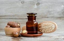 Apotheekfles met macadamia nootolie en houten haarborstel Ingrediënten van eigengemaakte schoonheidsschoonheidsmiddelen - gezicht stock fotografie