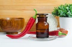 Apotheekfles met rode het uittrekseltint van de Spaanse peperpeper, infusie, olie en de verse peulen van de Spaanse peperpeper royalty-vrije stock afbeeldingen