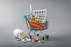 Apotheekzaken - boodschappenwagentje van pillen op grijze achtergrond stock afbeeldingen