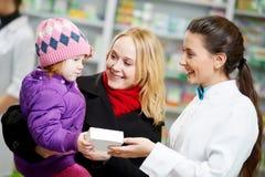 Apothekechemiker, -mutter und -kind im Drugstore lizenzfreie stockbilder