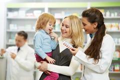 Apothekechemiker, -mutter und -kind im Drugstore