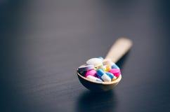Apothekenhintergrund auf einer schwarzen Tabelle mit messendem Band Tablets auf einem hölzernen Löffel Pillen Medizin und gesunde Lizenzfreie Stockfotos