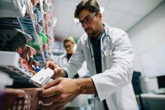 Apotheker die een drug op plank zoeken stock afbeelding