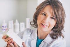 Apotheker die een geneeskunde in de drogisterij tonen stock foto