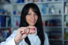 Apotheker die een pil houdt stock foto's