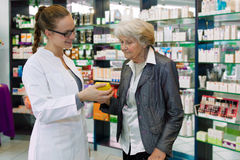 Apotheker die medicijn adviseren aan hogere patiënt. Stock Foto