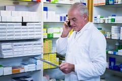 Apotheker die op mobiele telefoon spreken terwijl het controleren van geneesmiddelen Royalty-vrije Stock Foto