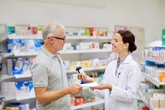 Apotheker en hogere mens het kopen drug bij apotheek royalty-vrije stock foto's