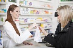 Apotheker en klant in apotheek Stock Afbeelding