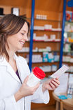 Apotheker Holding Medicine Bottle terwijl het Lezen van Voorschriftpa Stock Foto