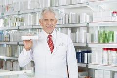 Apotheker Holding Medicine Box gegen Regale Lizenzfreie Stockfotografie