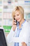 Apotheker Holding Prescription Paper bei der Anwendung des schnurlosen Telefons Lizenzfreies Stockfoto