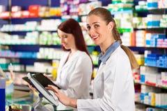 Apotheker met medewerker in apotheek stock foto's