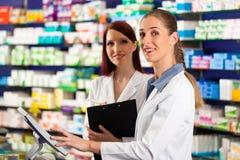 Apotheker mit Assistenten in der Apotheke Lizenzfreie Stockfotos