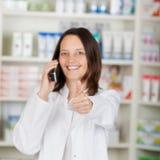 Apotheker Using Landline Phone beim Gestikulieren von Thumbsup Stockbild