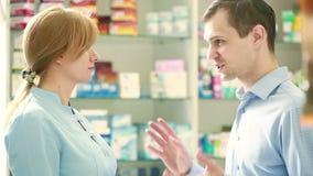 Apothekerfrau bietet dem Besucher eine Heilung an der Apotheke an stock video footage