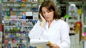 Apothekerfrau, die in der Apotheke am Telefon arbeitet stock footage