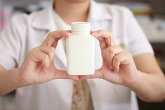 Apothekerhand, die Medizinflasche hält lizenzfreie stockfotos