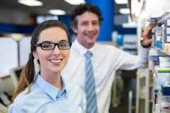 Apothekers die geneesmiddelen controleren op plank in apotheek royalty-vrije stock afbeelding