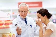 Apothicaire et client malade à la pharmacie Image libre de droits