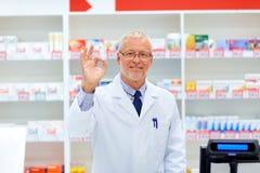 Apothicaire supérieur à la pharmacie montrant le signe correct de main Photos libres de droits