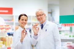 Apothicaires à la pharmacie montrant le signe correct de main Images stock