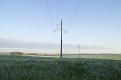 Apoya la línea de alto voltaje en el amanecer en las colinas Fotografía de archivo
