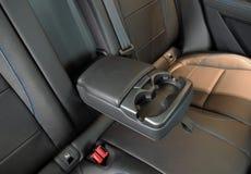 Apoyabrazos de centro plegables posteriores en interior de lujo del vehículo con cuero cosido fotografía de archivo libre de regalías