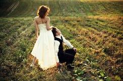 Apoyo - prepare los restos en las piernas de la novia en alguna parte en el campo fotografía de archivo