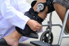 Apoyos de rodilla de la fijaci?n del fisioterapeuta de la pierna del hombre mayor con sentarse en la silla de ruedas, el concepto fotografía de archivo libre de regalías
