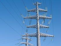 Apoyos grises del metal de la línea eléctrica de alto voltaje Imágenes de archivo libres de regalías