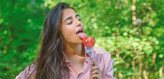 Appétit séduisant Femme complètement du désir mangeant la tomate La fille tient la fourchette avec la tomate mûre juteuse La fill photographie stock libre de droits