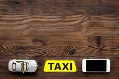 App για τη διαταγή ένα ταξί on-line με το παιχνίδι αυτοκινήτων και κινητός στο ξύλινο διάστημα άποψης υποβάθρου τοπ για το κείμεν Στοκ φωτογραφίες με δικαίωμα ελεύθερης χρήσης