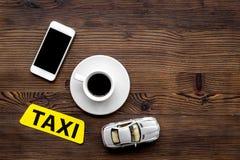 App для заказа такси онлайн с игрушкой автомобиля и чернь на деревянном взгляд сверху предпосылки размечает для текста Стоковые Фото