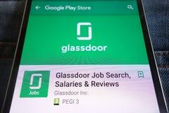 App de la búsqueda de trabajo de Glassdoor en la página web del Google Play Store exhibida en smartphone ocultado en bolsillo de  imagenes de archivo