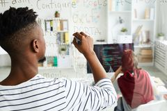App developer writing code on glassy wall. Rear view of modern African-American male app developer writing code on glassy wall while working on new software royalty free stock images