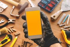 App elegante del teléfono de la manitas, reparador que sostiene el teléfono móvil a disposición fotos de archivo libres de regalías