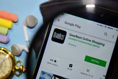 App en línea del revelador de las compras de GearBest con magnificar en la pantalla de Smartphone foto de archivo libre de regalías