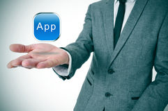 App icon. A businessman with an icon with the word app in his hand Royalty Free Stock Photo