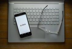 APP lâche à un téléphone portable se reposant sur un ordinateur portable à côté des verres images libres de droits