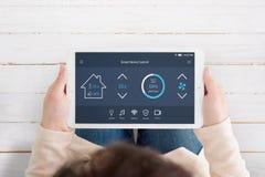 App moderno, automatizado do controle da casa com inteligência artificial na exposição da tabuleta nas mãos da mulher fotos de stock royalty free