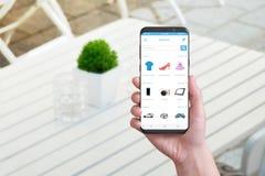 App que hace compras en línea en el teléfono elegante con los bordes redondos foto de archivo