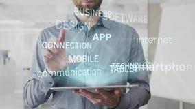 App, Smartphone, Internet, Kommunikation, Technologiewortwolke gemacht als Hologramm benutzt auf Tablette vom bärtigen Mann, auch stock footage