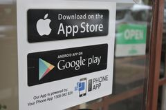 App Store and Google Play stickers on a shop door. A digital distribution platforms for Apple and Android operating systems allowing users to browse and royalty free stock photo